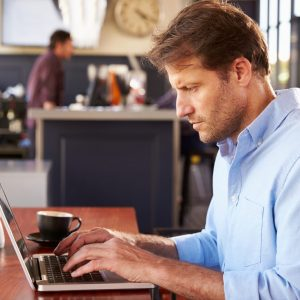 man on laptop using the Coaching Others for Performance Excellence program
