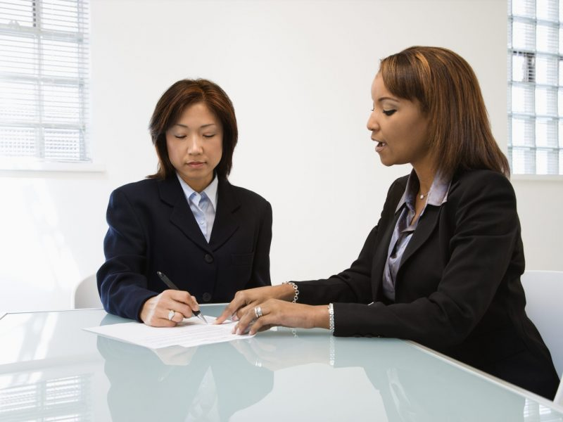 photo of business women talking; get along with your boss