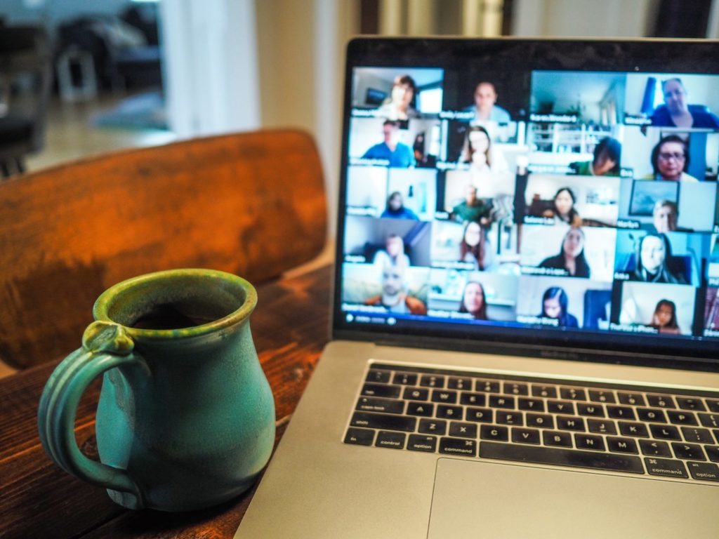 photo of the virtual workplace, laptop screen with images on everyone on a remote meeting