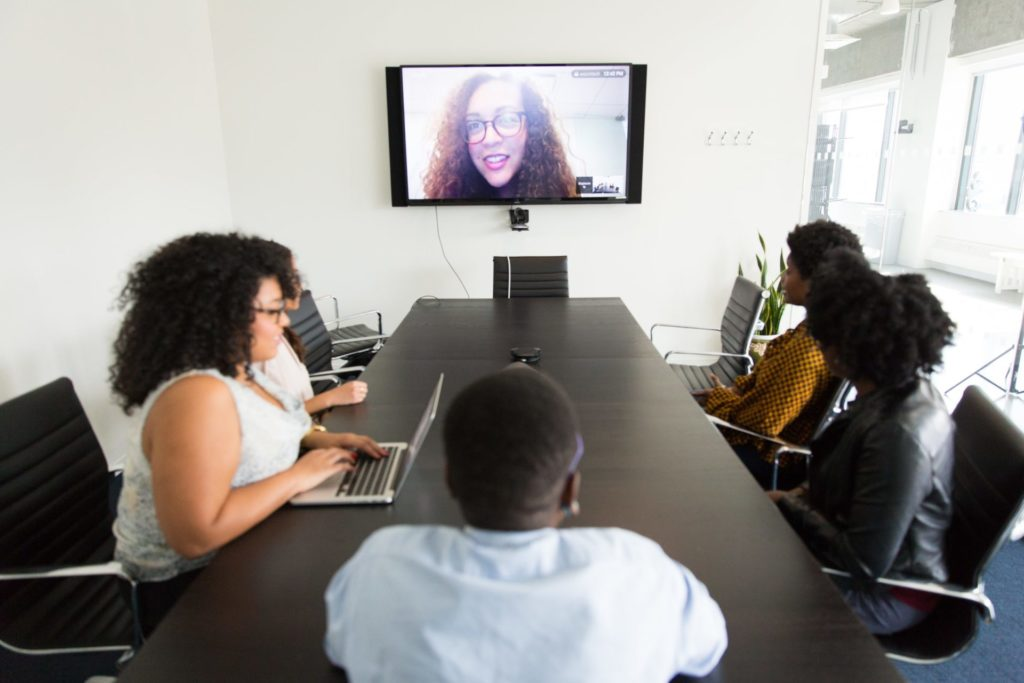 photo of people sitting at table talking to someone remotely