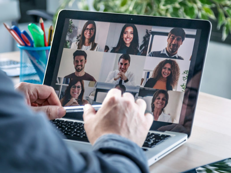 man on laptop talking to coworkers through video chat